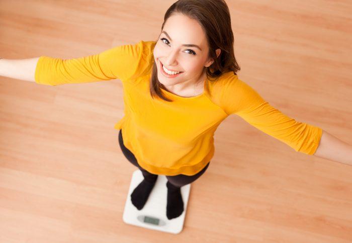 Счастливая девушка на весах в желтом свитре