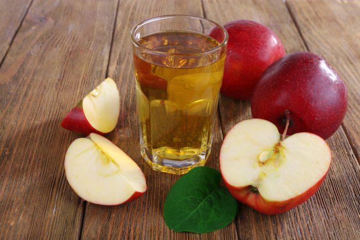 Стакан яблочного сока возле яблок