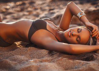 Загорелая девушка в купальнике с браслетом лежит на песке