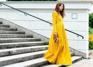 Девушка идет по ступенькам в длинном желтом платье