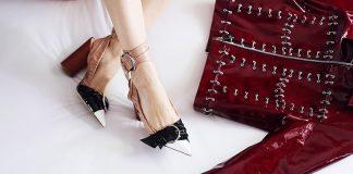 Босоножки на женских ножках возле лакированной красной ветровки