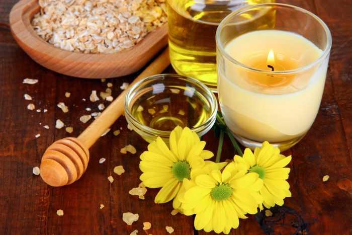 Цветы на поверхности с овсянкой, медом и свечой в стакане