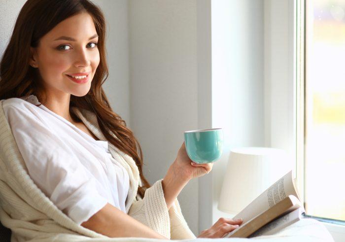 Девушка с чашкой чая и книгой сидит у окнам