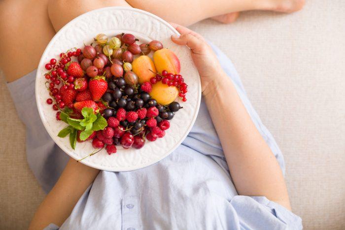 Девушка держит тарелку с фруктами и ягодами