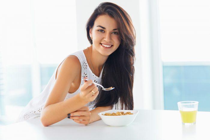 Девушка ест кашу и улыбается
