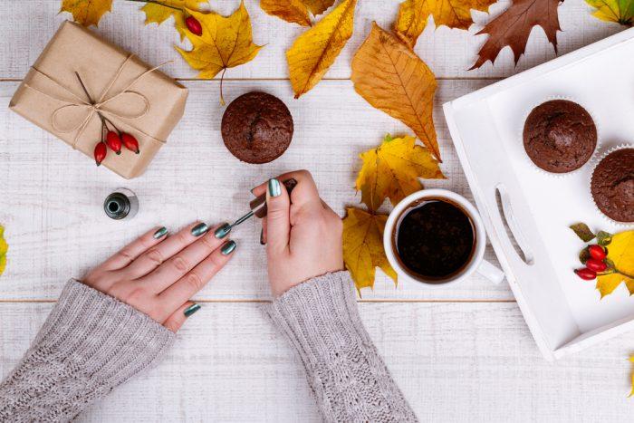 Девушка красит ногти на поверхности с кофе, кексами и желтыми листьями