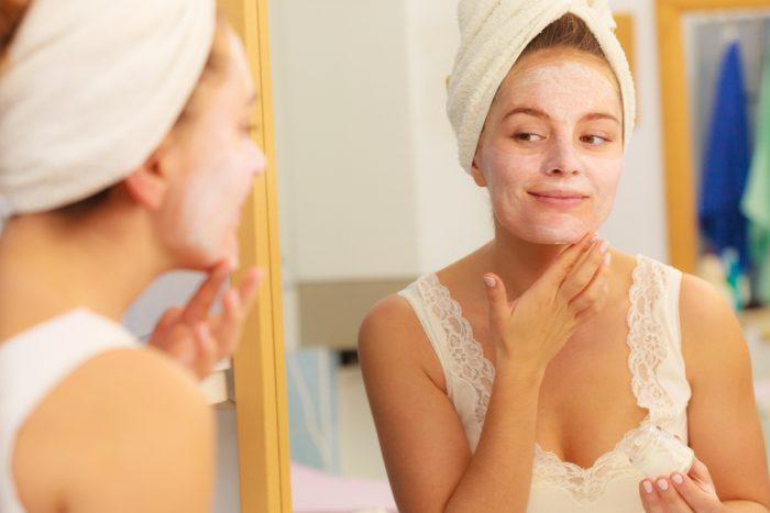 Девушка перед зеркалом с маской для лица