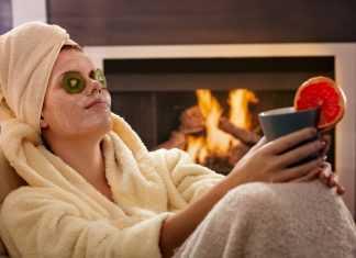 Девушка с чашкой в халате с полотенцем сидит с маской на лице с киви