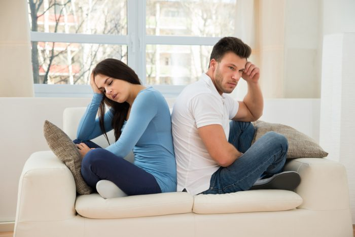 Девушка с парнем сидят на диване отвернувшись один от другого