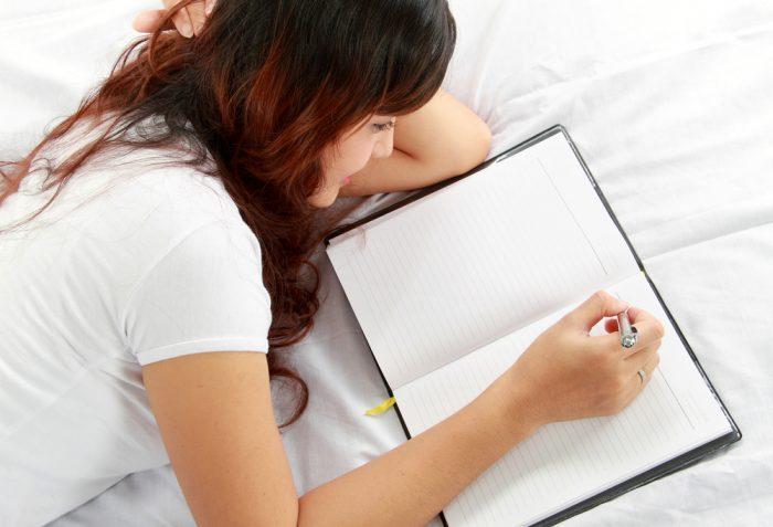 Девушка в белой футболке лежит с блокнотом