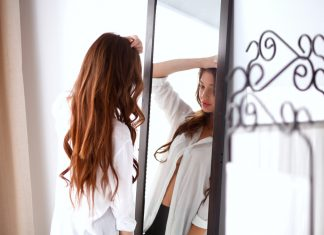 Девушка в белой рубашке стоит перед зеркалом