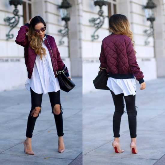 Девушка в черных порваных джинсах и темно розовом бомбере