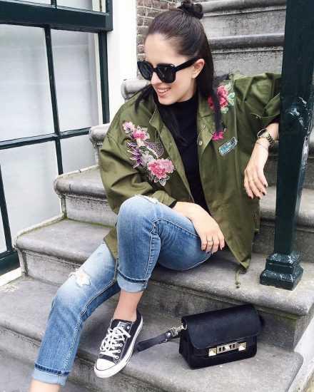 Девушка в джинсах и зеленом бомбере сидит на ступеньках