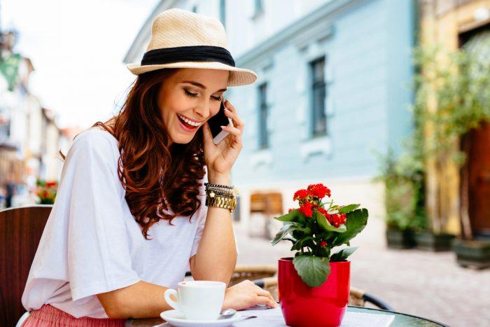 Девушка в шлпе в кафе говорит по телефону