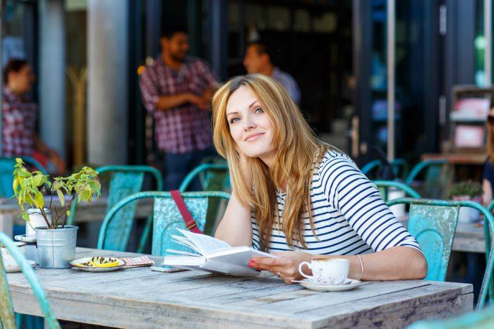 Девушка в кафе сидит с книгой