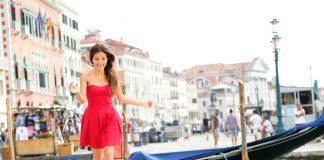 Девушка в красном платье бежит по городу