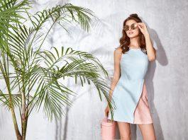 Девушка в очках, в розово-голубом платье возле цветка-пальмы