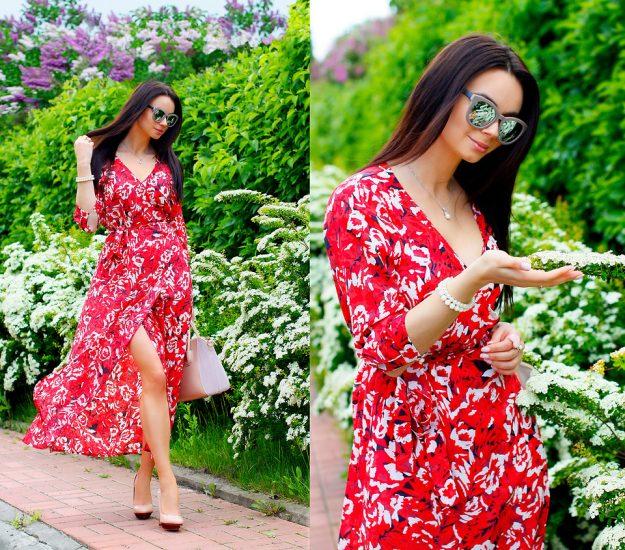 Девушка в красном платье с разрезом и в белых цветах в саду