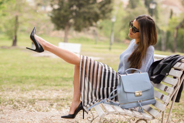 Девушка в шпильках и полосатой юбке сидит на лавочке