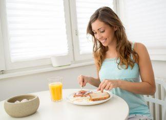 Девушка завтракает сидя за столом