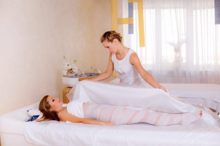 Девушку в салоне, после обертиванния накрывают одеялом