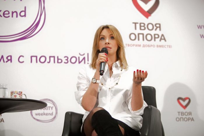 Актриса «Студии Квартал-95» Елена Кравец сидит в белой блузке и говорит в миктофон