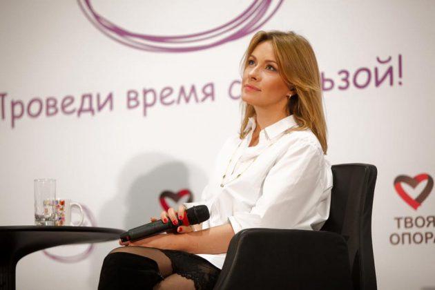 Актриса «Студии Квартал-95» Елена Кравец в белой блузке с миктофоном