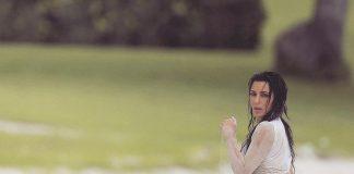Ким Кардашьян сидит на песке в бикини и футболке