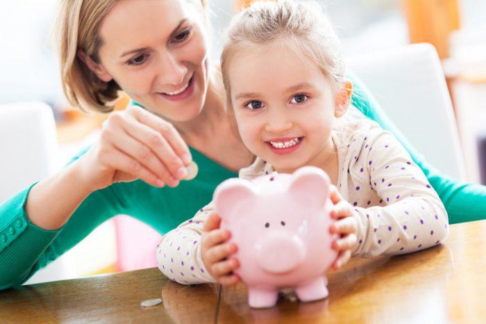 Мама с дочкой ложат деньги в копилку