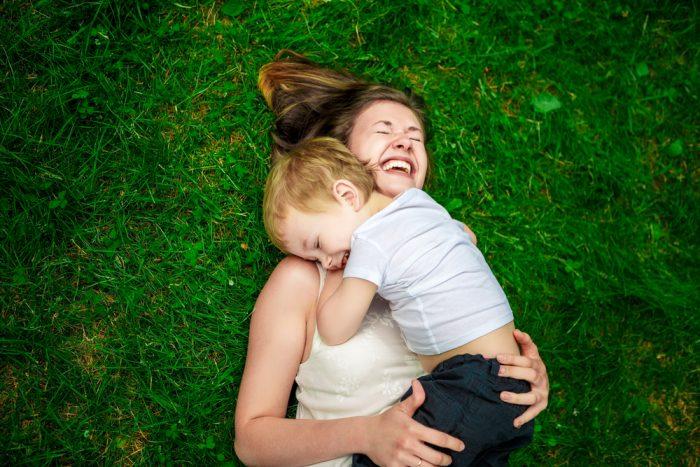 Мама в обнимку с сыном на траве смеются
