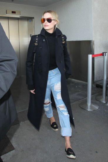 Марго Робби в джинсах и черном пальто