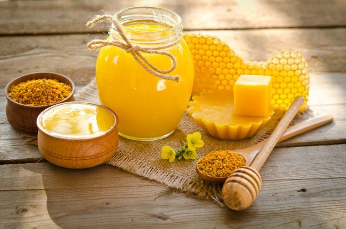 Мед в банке, в мисочке, соты и воск на деревянно поверхности