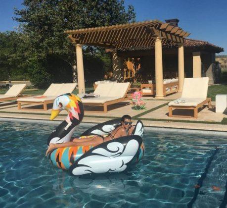 Кортни Кардашян в бассейне на надувном лебеде