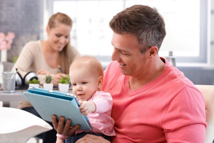 Отец с ребенком сидит перед планшетом