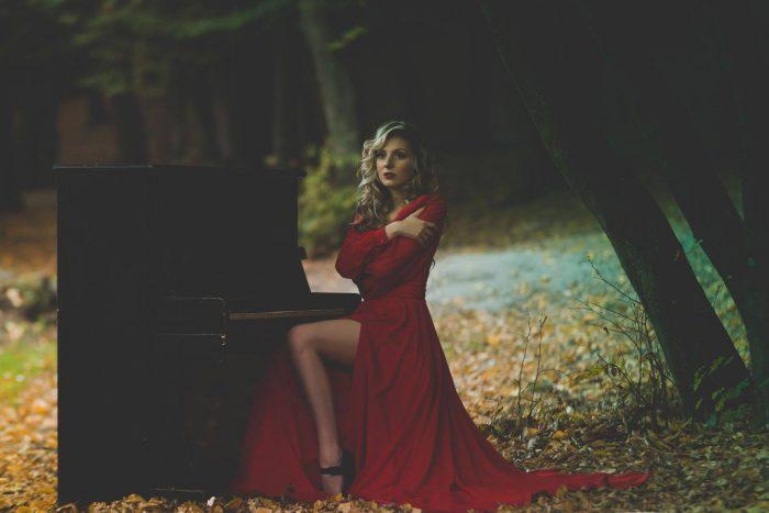 Певица Talina (Талина) в красном длинном платье на природе возле пианино