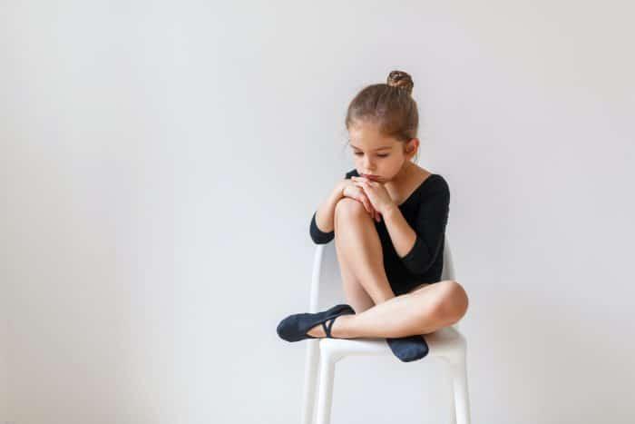 Расстроенная девочка на стуле в костюме балерины