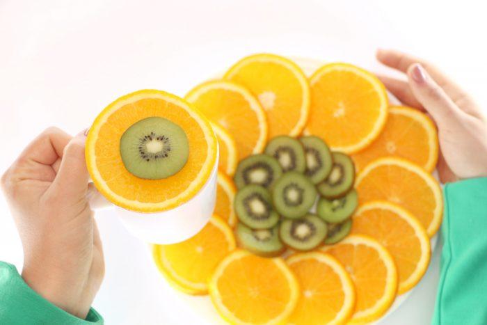 В женских руках тарелка с кольцами апельсина и киви