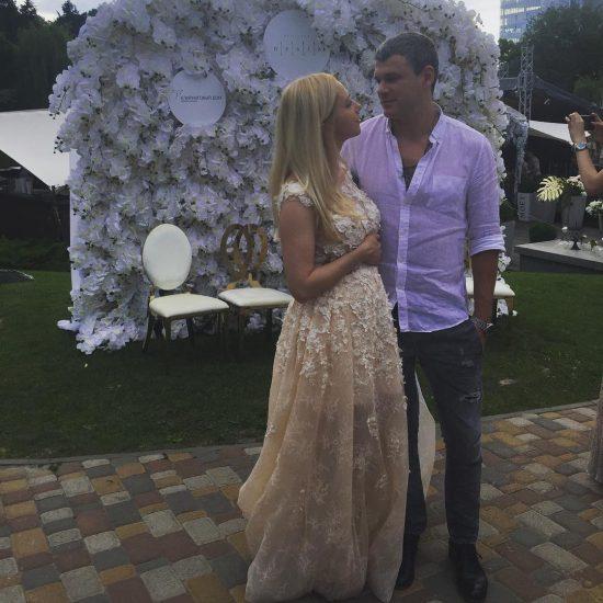 Тоня Матвиенко и Арсен Мирзоян на фоне стены в цветах