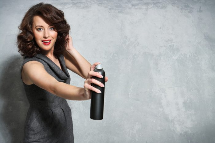 Женщина в сером платье с лаком для волос