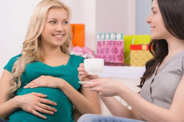 Беременная девушка пьет чай с подругой
