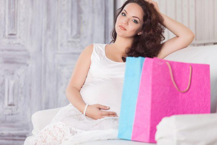 Беременная женщина на диване с покупками
