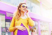 Беременная девушка в фиолетовом платье и желтой кофте и в очках говорит по телефону на улице