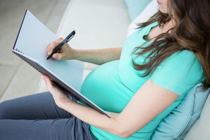 Беременная девушка делает запись в блокноте