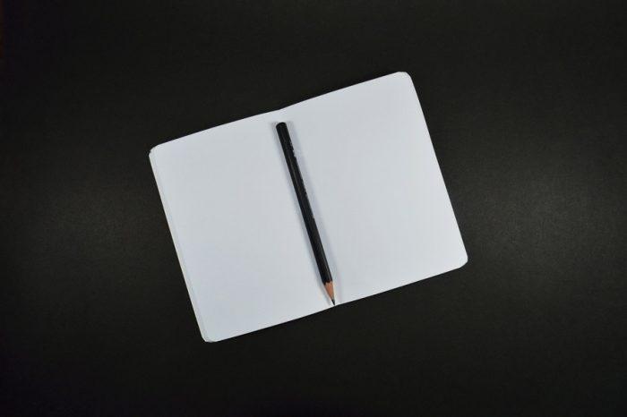 блокнот и карандаш на черном фоне