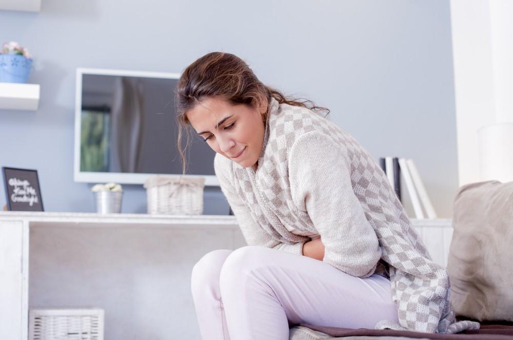 Девушка дома сидит держась за живот