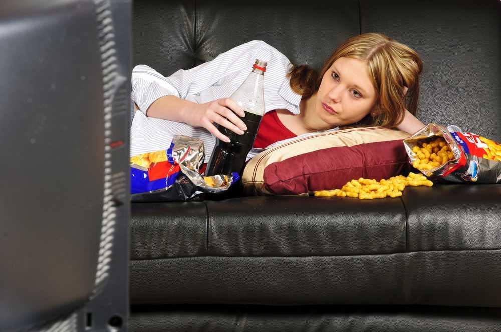 девушка лежит перед телевизором с газировкой и чипсами