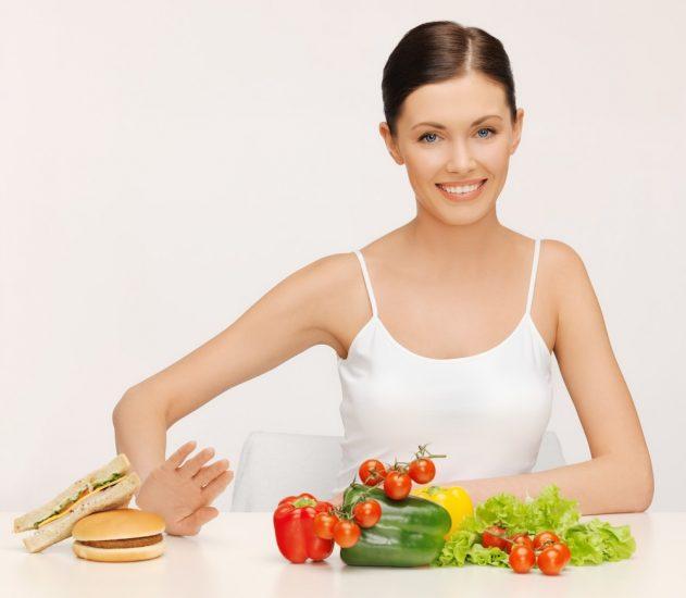 Девушка перед овощами отодвигает гамбургеры