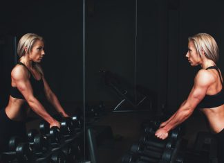 девушка в тренажерном зале смотрит в зеркало
