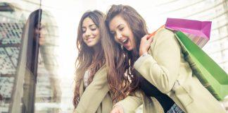 Девушки в одинаковых одеждах с покупками у витрины