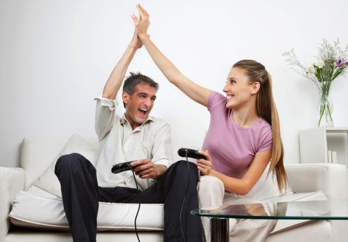 мужчина и женщина играют в приставку